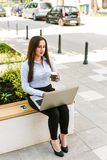 Young Businesswoman Using Laptop Outdoor While Drinking Coffee to go. Young Business woman Using Laptop Outdoor While Drinking Coffee to go Royalty Free Stock Images