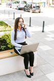 Young Businesswoman Using Laptop Outdoor While Drinking Coffee to go. Young Business woman Using Laptop Outdoor While Drinking Coffee to go Royalty Free Stock Image