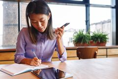 Young businesswoman using loudspeaker on mobile phone Stock Image
