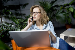 Young businesswoman using mobile phone while working with laptop Stock Image