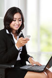 Young businesswoman using mobile phone while working in the offi Royalty Free Stock Image