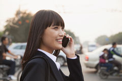 Young businesswoman using the phone outside on the street in Beijing Stock Image