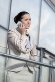 Young businesswoman using smart phone at office railing Stock Photos