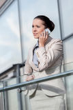 Young businesswoman using smart phone at office railing Royalty Free Stock Photos