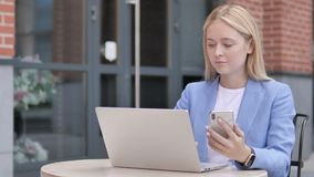 Young businesswoman using smartphone and laptop, sitting outdoor stock footage
