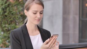 Young Businesswoman Using Smartphone Sitting Outdoor. 4k high quality, 4k high quality stock footage