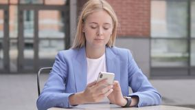Young Businesswoman Using Smartphone Sitting Outdoor. 4k high quality, 4k high quality stock video