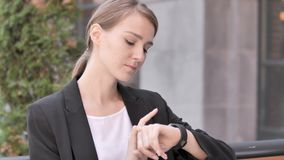 Young Businesswoman Using Smartwatch Sitting Outdoor. 4k high quality, 4k high quality stock footage
