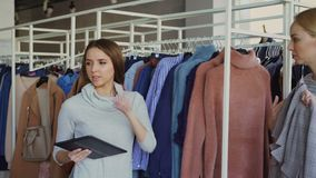 Young businesswoman is using tablet while checking goods in her clothing store. Assistant is coming with garment and stock footage