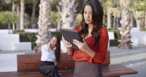 Young businesswoman using a tablet outdoors. Stylish attractive young businesswoman using a tablet outdoors in an urban square concentrating as she browses the stock video