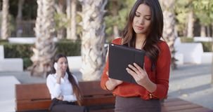 Young businesswoman using a tablet outdoors. Stylish attractive young businesswoman using a tablet outdoors in an urban square concentrating as she browses the stock footage
