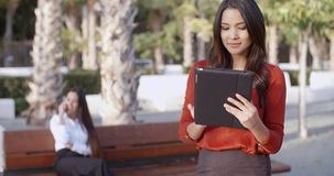 Young businesswoman using a tablet outdoors. Stylish attractive young businesswoman using a tablet outdoors in an urban square concentrating as she browses the stock video footage