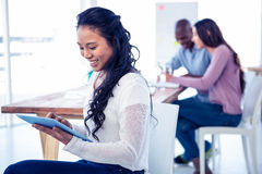 Young businesswoman using tablet PC with colleagues in background Stock Images