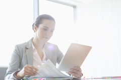 Young businesswoman using tablet PC while reading book in office Stock Photography