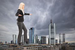 Businesswoman walking on a rope, with Frankfurt in the backgroun Stock Photo