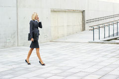 A young businesswoman is walking on the street Royalty Free Stock Image