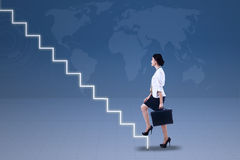 Young businesswoman walking up on stairs. With world map background Royalty Free Stock Image