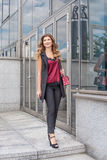 Young businesswoman walks out of the office with a red handbag Stock Image