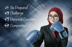 Young businesswoman wearing boxing gloves punching to success. Stock Image