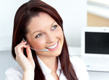 Young businesswoman wearing earpiece in her office Royalty Free Stock Photos