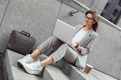 Business casual. Young lady in eyeglasses sitting on stairs on the city street with cup of coffee browsing laptop joyful stock photo