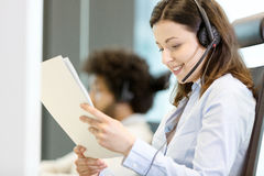 Young businesswoman wearing headset while reading document in office Stock Image