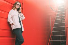 Young businesswoman wearing in pink denim jacket is standing and talking on mobile phone. Telephone conversations. In background bright red wall and ladder stock photo