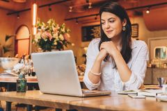 Businesswoman sitting in cafe at table,looking on screen of computer, smiling. Distance work. Online marketing,education. Young businesswoman wearing in shirt Royalty Free Stock Photos