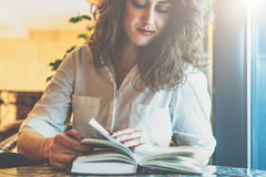 Young businesswoman in white shirt sitting at table and reading book. Girl leafing through book Royalty Free Stock Photos