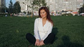 Young businesswoman in white suit sitting and meditating outdoor