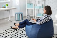 Free Young Businesswoman With Laptop Sitting On Beanbag Chair In Office Stock Photos - 151334913