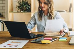 Young businesswoman woman is sitting at kitchen table and uses laptop, working, studying. On table tablet computer Stock Photography