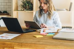 Young businesswoman woman is sitting at kitchen table and uses tablet computer, working, studying. Royalty Free Stock Photos
