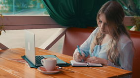 Young businesswoman work in cafe using laptop writing in notebook. 4K stock video