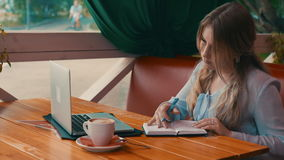 Young businesswoman work in cafe using laptop writing in notebook. 4K stock video footage