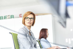 Young businesswoman working on computer with colleague in background at office Royalty Free Stock Photos