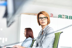 Young businesswoman working on computer with colleague in background at office Stock Photos