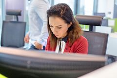 Young businesswoman working at computer desk with colleague in background Stock Photo