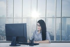 Young businesswoman working with computer. While sitting by the window. Shot in the office Royalty Free Stock Photos