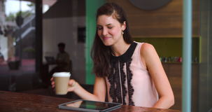 Young Businesswoman Working On Digital Tablet In Coffee Shop. Young businesswoman sitting in coffee shop working on digital tablet.Shot on Sony FS700 at frame stock video footage