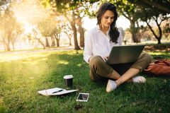 Young businesswoman working on her notebook in park. Freelancer female sitting on grassy lawn using laptop computer with her diary royalty free stock photo