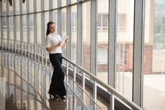 Young businesswoman working on ipad while standing by window in office. Beautiful young female model in bright office stock photo