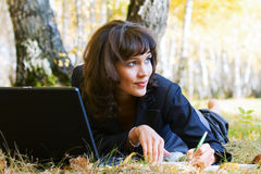 Young fashion businesswoman with laptop working outdoor Royalty Free Stock Images