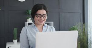 Young businesswoman working on laptop. At office stock video footage