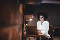 Young businesswoman working late on laptop in office royalty free stock image