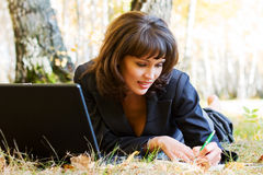 Young fashion businesswoman with laptop working outdoor Royalty Free Stock Image