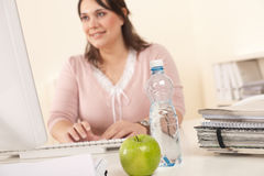 Young businesswoman working at office. Focus on apple and bottle of water on table Royalty Free Stock Photo