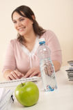 Young businesswoman working at office. Focus on apple and bottle of water on table Stock Images