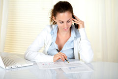 Young businesswoman working at office. While conversing on cellphone at office - copyspace Royalty Free Stock Photos