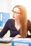 Young businesswoman working in office with papers. Young businesswoman working in office at sunny day with documents Stock Photo